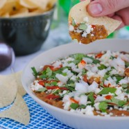 5 Ingredient Bean & Chorizo Dip - Chorizo, pinto beans, tomatillo salsa, lime juice and sour cream combine to make a game day dip the whole crowd will love!