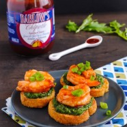 Chipotle Shrimp & Arugula Pesto Crostini - A fresh and elegant summer party bite. Crunchy bread, herby homemade arugula pesto, and chipotle glazed shrimp. | foxeslovelemons.com
