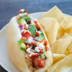 Bacon-Wrapped Sonoran Hot Dogs - Hot dogs wrapped in bacon, tucked into buns filled with beans, avocado, lime sour cream and other Mexican-inspired toppings! | foxeslovelemons.com