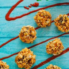 Peanut Butter-Sriracha Popcorn Balls - An easy, spicy and sweet treat made with popcorn, sriracha, peanut butter, ginger, peanuts and sesame seeds. | foxeslovelemons.com